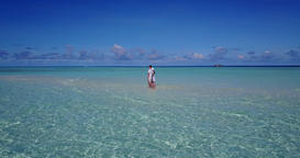 Romantic couple sunbathe on luxury coast beach holiday by blue ocean and white sandy background of Live Action