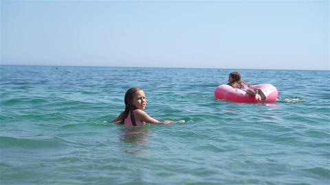 Little girls having fun at tropical beach during summer vacation playing Live Action