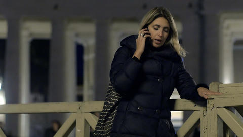 cute young woman is having conversation with mobile phone in the evening Footage