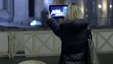 young woman is making photos to St. peter church in the night with tablet pc Footage