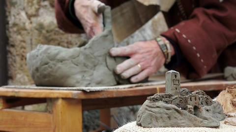artisan man modelling a clay sculpture in Italy Live Action
