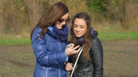 two girls are having fun looking at something funny on smart phone Footage