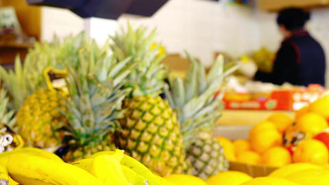 fresh ananas fruits in the market with woman working in the background Footage