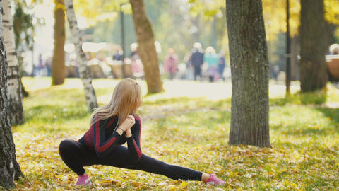 Sexy Attractive female blonde bikini-fitness model stretching in the autumn park Footage