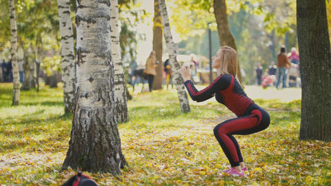 Sexy Attractive female blonde bikini-fitness model stretching in the autumn park Filmmaterial