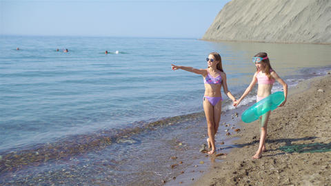 Little happy funny girls have a lot of fun at tropical beach playing together Live Action