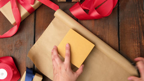 process of packing boxes in brown kraft paper on a wooden table, holiday gifts Live Action
