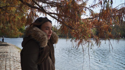 A lovely woman standing alone beside lake on a park Live Action