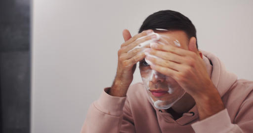 young caucasian man washing face with facial cleanser face wash soap in bathroom Live Action