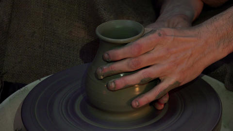 Hands working on pottery wheel, shaping a clay pot Footage