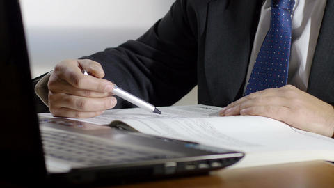 businessman at work with laptop is checking a printed list on paper sheets Footage
