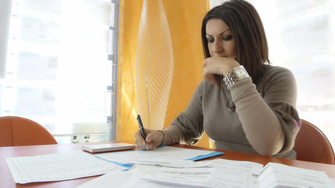 businesswoman at work with problems on the budget with calculator Live Action
