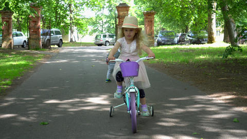 Stylish girl rides bike in Park. Happy child smiling. Little brother walking Live Action