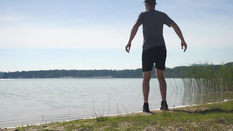 Man runner stretching at lake. Running man stop for stretching his body. Daily workout in attractive Live Action