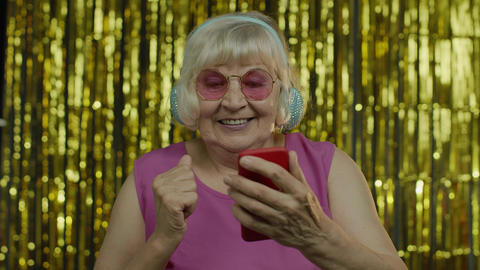 Stylish happy senior old woman holding cell phone, listening to music in Live Action