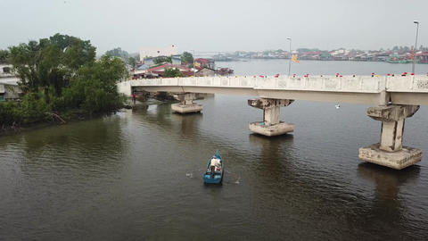 Aerial Malays fisherman row the boat cross the bottom of the pedestrian bridge Live Action
