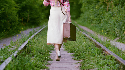 Lonely tourist woman with retro suitcase walking on old railway back view Live Action