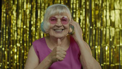 Senior old woman dances, listens music on headphones. Having fun, smiling Live Action