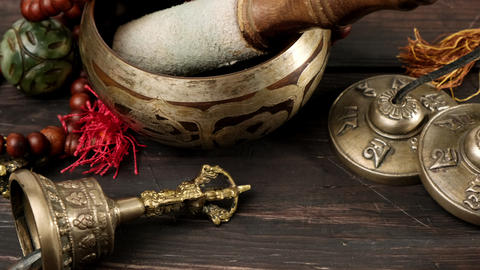 Tibetan singing copper bowl with a wooden clapper on a brown wooden table, objects for meditation Live Action