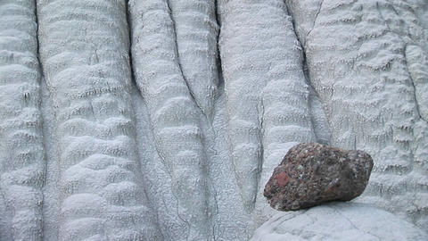 Medium-shot of a granite rock sitting at the base of a white limestone wall Footage