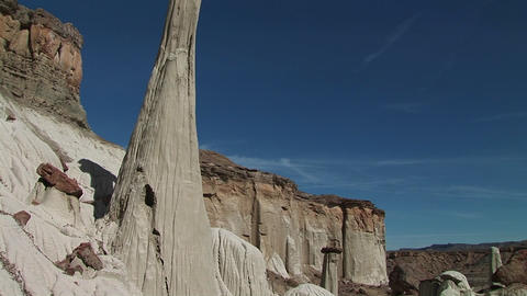 Pan-up from a desert floor to a boulder balanced atop a... Stock Video Footage