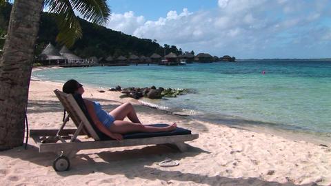 A woman relaxes on a beach chair on a tropical beach Stock Video Footage