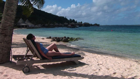 A Woman Relaxes On A Beach Chair On A Tropical Beach stock footage