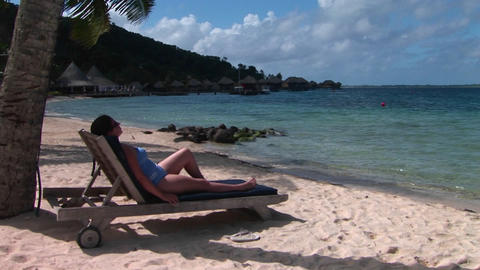 A woman relaxes on a beach chair on a tropical beach Stock Video Footage