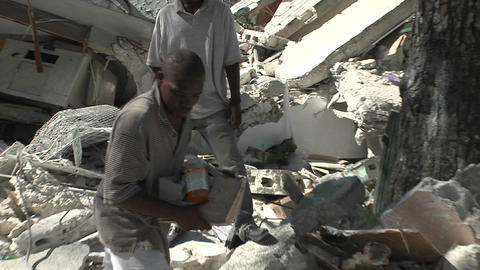 People remove bricks from a collapsed building dur Footage