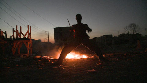 A man dances in silhouette in front of a fire Footage