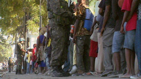 Long lines of refugees wait on the streets of Hait Stock Video Footage