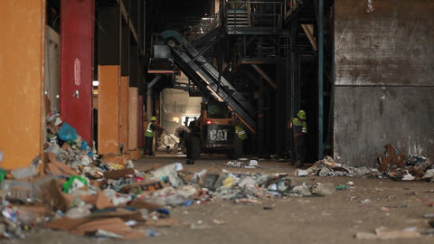 A skip loader picks up trash at a recycling center Stock Video Footage