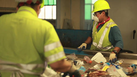 Workers sort trash at a recycling center Stock Video Footage