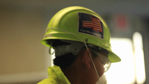 An American factory worker wears a helmet with a f Footage
