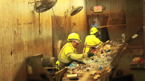 Workers in a recycling center sorting trash on con Footage