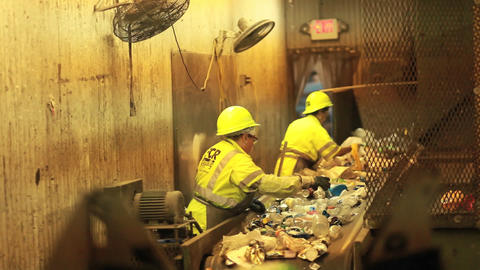 Workers in a recycling center sorting trash on con Stock Video Footage