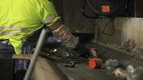Workers sort trash on a conveyor belt at a recycli Footage