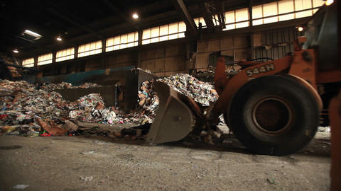Skip loader shovels recycling at a factory Footage