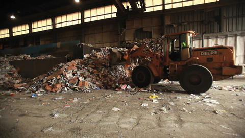 Skip loader shovels recycling at a factory Footage