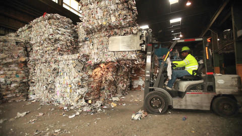 A skip loader moves aluminum cans at a recycling c Stock Video Footage