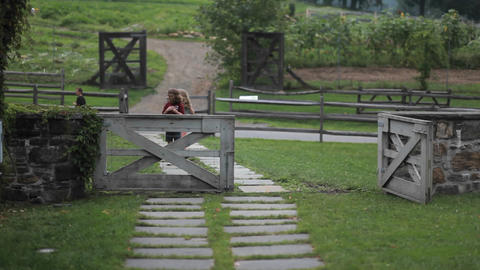 Two children play on a path behind a fence in an a Stock Video Footage