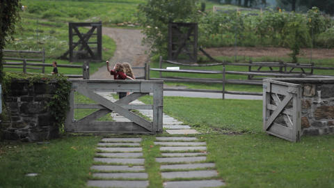 Two children play on a path behind a fence in an a Footage