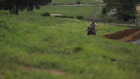 A man pushes a piece of farm equipment in an agric Stock Video Footage