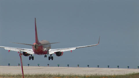 A jet takes of from a runway as another jet lands Stock Video Footage