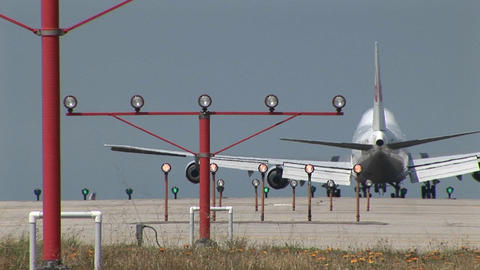 A 747 jet lands on an airport runway behind lights and... Stock Video Footage