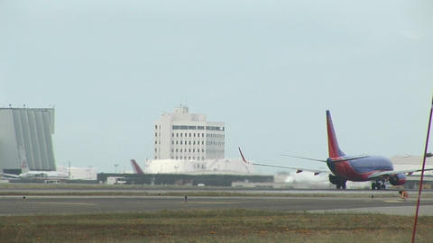 Airplanes move along the runway at a large urban airport Stock Video Footage