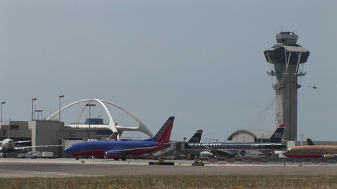 Airplanes taxi along the runway at Los Angeles... Stock Video Footage