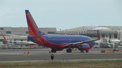 A Southwest Airlines jet sits on an airport tarmac Live Action