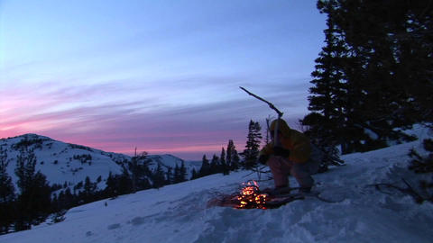 Panning-shot from snowy mountains to a hiker tending a campfire Footage