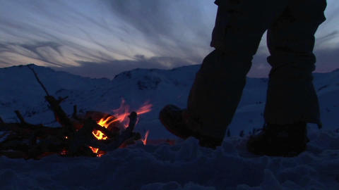 Close-up of a man's legs beside a campfire in winter Stock Video Footage